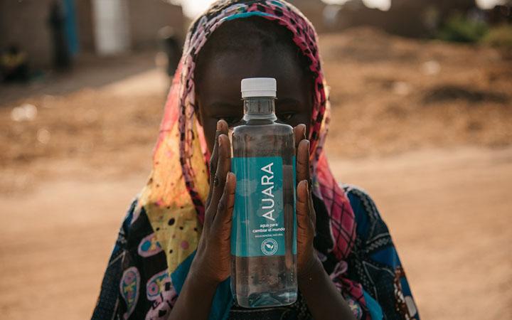 niña sujetando una botella de agua